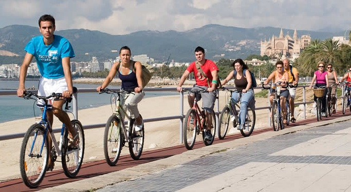 Turistes i residents pedalant pel passeig marítim